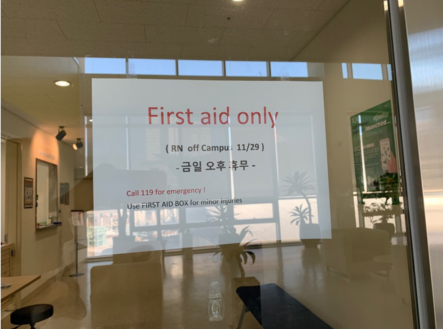 "IGC Health center's entrance. In the notice says, ""Fridays afternoon is closed day"". There is a First-Aid kit in front of the center's entrance, which is for minor injuries. Photo by: Jieun Yang"