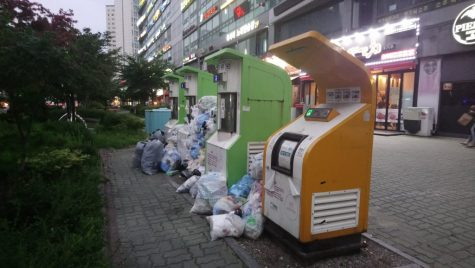 Trash piles up beside trash receptacles in Songdo. Incheon Metropolitan City plans to reduce the amount of trash produced per day by 32 tons before 2025. (Photo Courtesy of Google Images.)