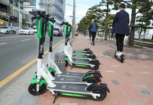Users pass by a shared company's electric kickboard parked on the beach of Gwangalli Beach in Suyeong-gu, Busan (Credit: Google Image)